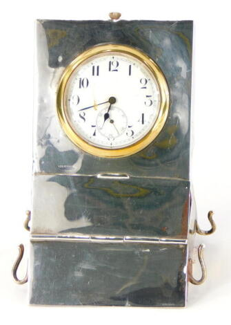 A George V silver mounted desk stand, of rectangular form, containing a pocket watch with brass bezel, a hinged lid enclosing a brush and two inkwells and two clips, possibly for a quill pen, Birmingham 1910.
