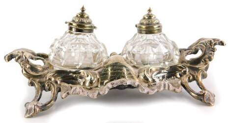 A Victorian silver ink stand, with rococo casting, insert with two cut glass inkwells, each with a hinged lid, presentation engraving, presented to Mrs Higgins on her marriage by Mr Wilson and the servants at The George Hotel, with the best wishes for her