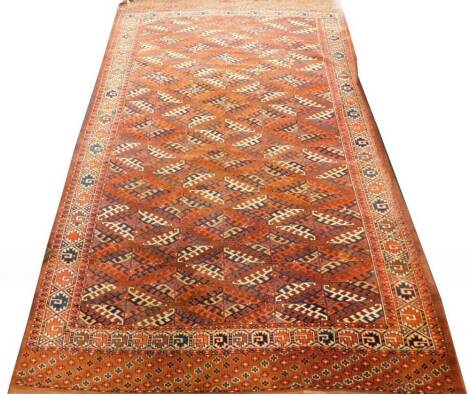 A Tekke Turkoman type carpet, with a lozenge design in blue and red, on a brown ground with one wide and one narrow border, 233cm x 200cm.