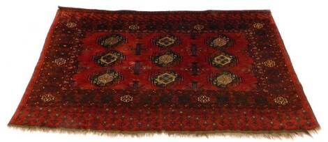 A Turkoman type rug, with a design of nine medallions on a red ground with multiple borders, 175cm x 100cm.