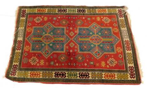 A Kazak` type rug, with two turquoise and red geometric medallions, on a red ground with one wide and various narrow borders, 146cm x 100cm.