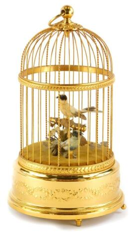 A 20thC Swiss musical bird cage, containing two feather clad birds, on the base decorated with swags, scrolls, etc., stamped to underside Reuge Music, Sainte-Coix Made in Switzerland, 5346, 32cm high.