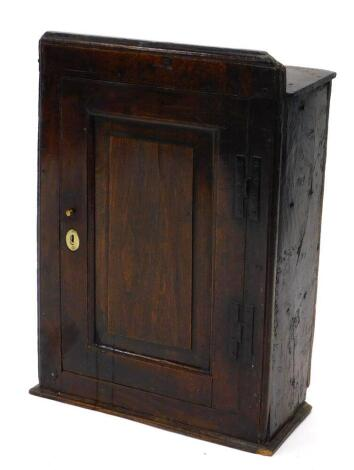 A late 17th/early 18thC oak wall cupboard, the top with a moulded edge above a single panelled door, with iron H shaped hinges, 68cm high, 47cm wide, 23cm deep.