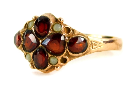 A 9ct gold garnet dress ring, the central four leaf clover design garnet with four moonstone borders and two oval cut amethyst sides, with shield engraved shoulders, ring size P, 2.5g all in.