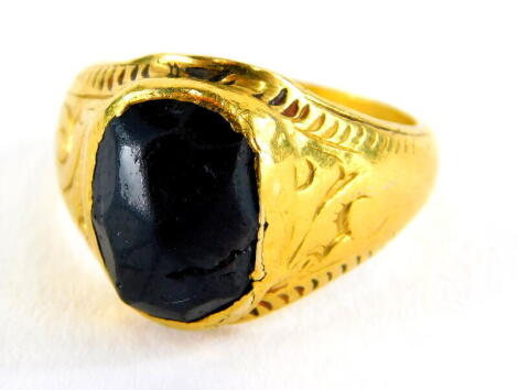 A garnet set signet ring, the setting of hammered design with scroll design shoulders and etched shoulders, yellow metal, unmarked, believed to be 22ct, ring size K, 6g all in.
