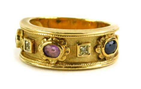A Brooks and Bentley amethyst and diamond 9ct gold dress ring, of Eastern design with central amethyst, a sapphire and a ruby, and two tiny diamonds, on hammered design border with import marks, ring size O½, 7g all in, boxed.