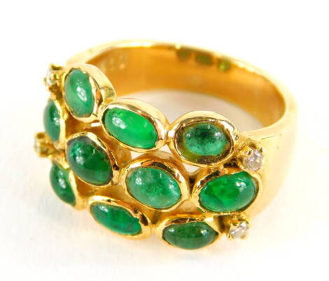 An emerald and diamond set dress ring, with three row design of cabachon emeralds, with four tiny diamonds, yellow metal, marked 750, ring size L, 7.2g all in.