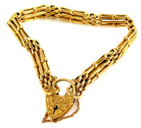 A late 19thC 9ct gold charm bracelet, the three row design bracelet, with hammered decoration and plain design links, 9cm wide, with a heart shaped padlock and safety chain, makers stamp MBS, 12.6g.