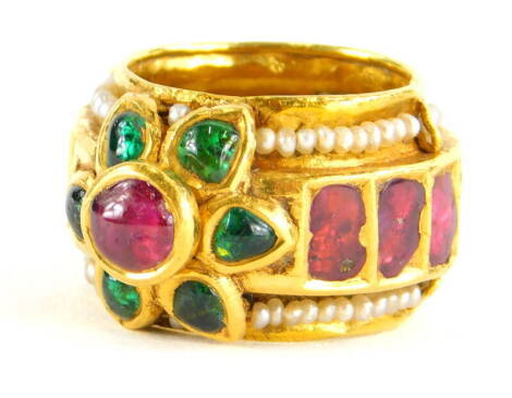 An Indian dress ring, set with various cabochon cut rubies, emeralds and seed pearls, the centre cluster in raised setting, the band set with various rough cut rubies, on a seed pearl surround, yellow metal, unmarked, ring size L, 12.1g all in.