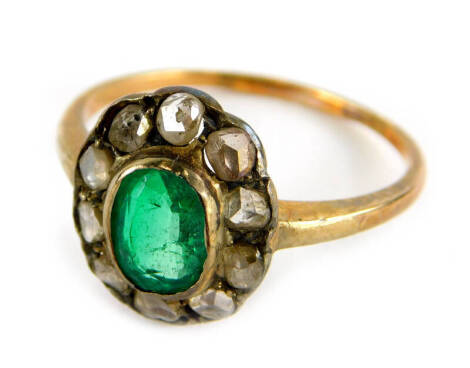 An emerald and diamond dress ring, in floral cluster with central oval cut emerald, surrounded by various diamonds chips, in yellow metal setting, on thin band, marked 585, ring size P, 2.6g all in.