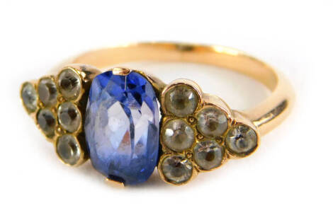 An Art Deco style ring, with oval cut pale blue sapphire, flanked by triangle staggered design set with six white sapphires, on a yellow metal band, unmarked, ring size J, 4.1g all in.