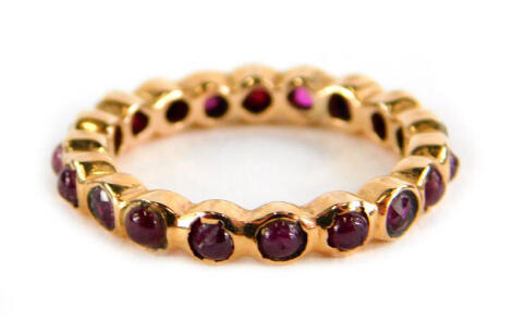 A garnet eternity ring, set with various cabochon cut stones, in a rose gold coloured setting, unmarked, ring size K½, 2.9g all in.