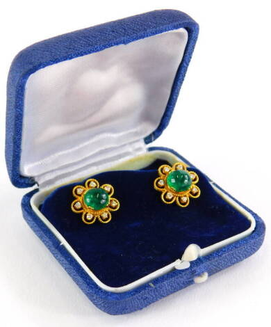 A pair of emerald and diamond cluster earrings, each set with central cabochon cut emerald with seven point flower surround, in rope twist design border, on a screw on butterfly back, yellow metal, the backs marked 18kt, earring head 1.4cm wide, 7.2g all
