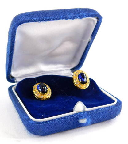 A pair of sapphire and diamond earrings, each with central cabochon cut sapphire in four claw setting, surrounded by tiny diamonds, yellow metal, on butterfly backs, marked 585, earring 1.5cm wide, 3.6g all in.