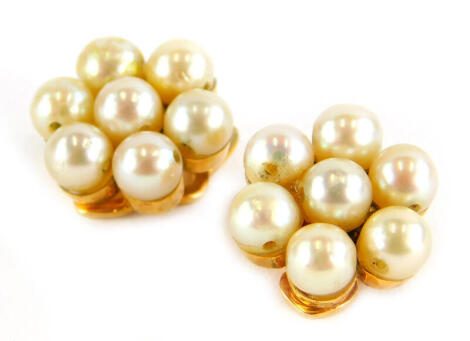 A pair of pearl earrings, each in a cluster group, with seven pearls, in a yellow clip on metal frame, unmarked, 3.7g all in.