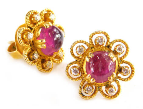 A pair of ruby and diamond cluster earrings, each set with central cabochon cut ruby with seven point flower surround, in rope twist design border, on a screw on butterfly back, yellow metal, the backs marked 18kt, earring head 1.4cm wide, 7.6g all in.