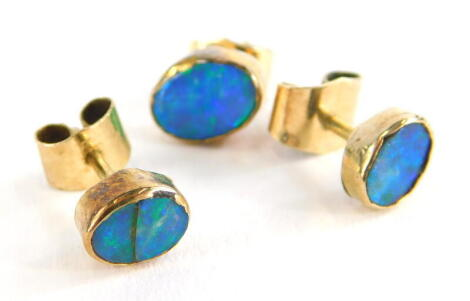 Three various opal set earrings, each set with oval cut opals in rub over setting, each with butterfly backs, yellow metal, unmarked, 1.9g all in.