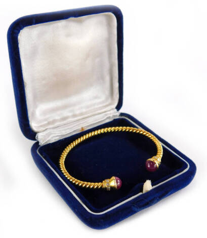 A torc bangle, the bangle ends set with cabochon cut ruby, and diamond surround, on a spiral turned bracelet, yellow metal, unmarked, 6cm wide, 16.3g all in.
