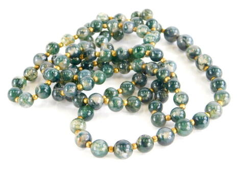A jadeite graduated beaded necklace, each bead of pale colour with dark green splashes, on string, with gold coloured bead breaks, 58cm long overall.