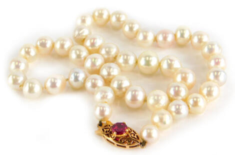 A natural pearl necklace, the oval clasp set with garnet in four claw setting, yellow metal, unmarked, the pearls approx 5mm to 8mm, 41cm long overall, 39.8g all in.