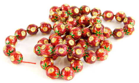 An enamel beaded necklace, the spherical beads in red enamel with green enamel leaf design, each set with white paste stones, on a gold coloured clasp, 66cm long overall. (AF)