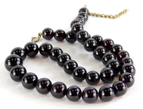 A garnet necklace, with graduated spherical beads, the largest 1cm wide, the smallest 8mm wide, on clear string, with silver clasp, 44cm long overall.