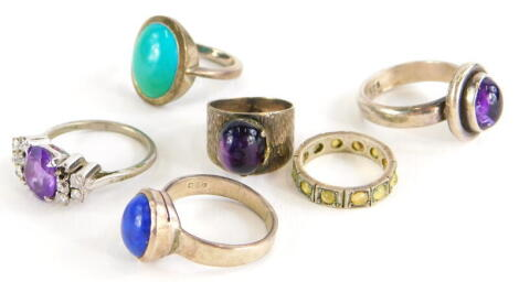 Various silver dress rings, to include silver and lapis set dress ring, ring size O, a silver and turquoise set dress ring, ring size M, a silver and purple agate set dress ring, ring size G, a silver and amethyst dress ring, ring size Q, a silver and imi