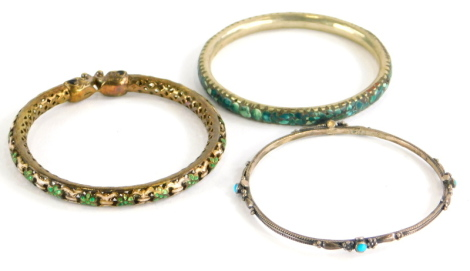 Three bangles, to include a silver bangle set with turquoise stones, 6.5cm diameter, a silver gilt an enamel elephant bangle, 6.5cm diameter and a further example set with fragments of turquoise, stamped made in India. (3)