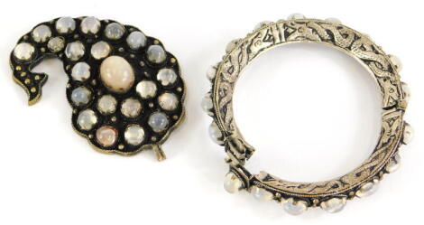 Two items of moonstone jewellery, to include an abstract pendant, darkened to front set with various moonstones, on white metal backing, unmarked, 7cm high, and a similar designed hinged bangle, with steel band. (2)