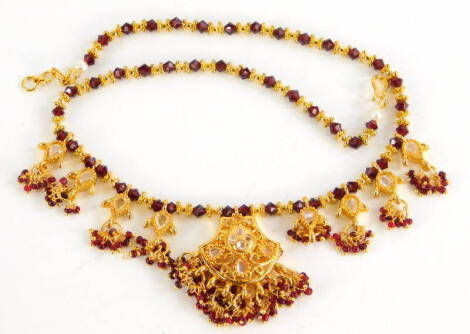 An Indian costume jewellery necklace, the red beaded necklace chain, with four drop sections each set with clear beads, gold plated, 39cm long overall.