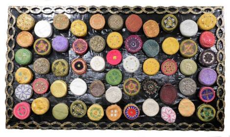 An impressive collection of Kufi hats of various embroidered coloured design, (57), together with a hand made papier mache display panel, 132cm x 229cm.
