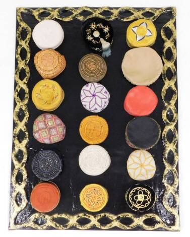 A collection of Kufi hats of various embroidered coloured design, (18), with a hand amde papier mache display panel, 94cm x 130cm.