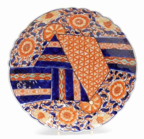A 19thC Imari dish, of floral circular form, profusely decorated with flowers and a geometric pattern predominately in orange and blue, with floral decoration verso, and single line mark to the circular foot, 32cm wide. (AF)