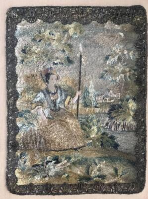 A Georgian petit point needlework silk picture, with silver filigree lacework border depicting a seated lady with crinoline dress and bonnet and buildings in the distance, 18cm x 14.5cm, gilt and glazed frame.