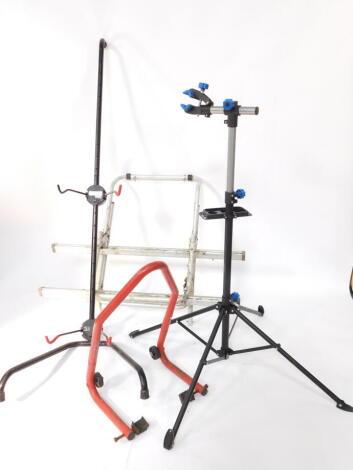 A Crivit Sports bicycle repair stand, FN-1290., a bike tree, and a bike rack. (3)