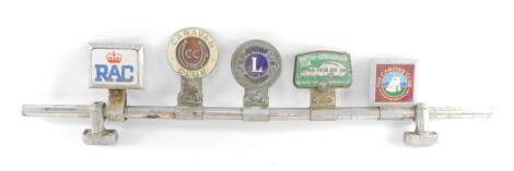 A car badge bar holding five badges, for RAC., Caravan Club., Lion's International., British Caravanner's Club., and The Camping Club.
