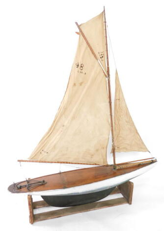 A wooden scale model of a single masted yacht, fully rigged, on a stand, 138cm wide.