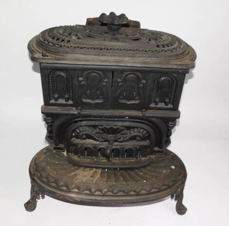 A Victorian cast iron kitchen range by The Columbian Stove Works., of oval form, with a pierced shell and scroll decorated cover, cast sliding doors and drawer, raised on a shaped oval base, on cabriole legs, 59cm high, 53cm wide, 57cm deep. Auctioneer No