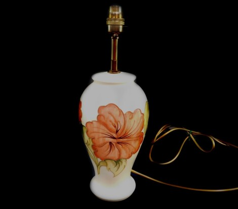 A Moorcroft pottery table lamp decorated in the Hibiscus pattern, of baluster form, decorated against a cream ground, impressed marks, 36.5cm high.