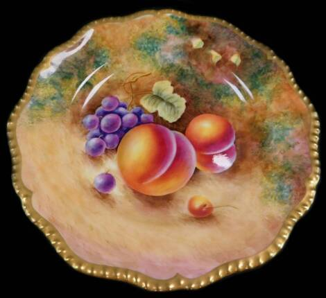 A Royal Worcester porcelain cabinet plate, signed Leaman, painted with peaches and black grapes, 22cm diameter.