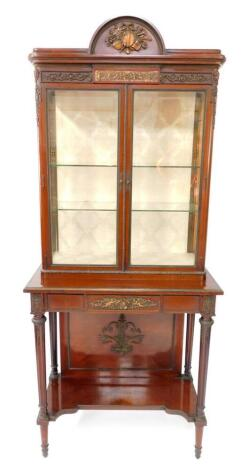 A late 19thC Louis XVI style mahogany vitrine, with metal mounts, the domed pediment cast centrally with musical instruments and flowers, over a frieze set with a panel of putti, flanked by scrolling flowers above two glazed doors, set with astragal glass