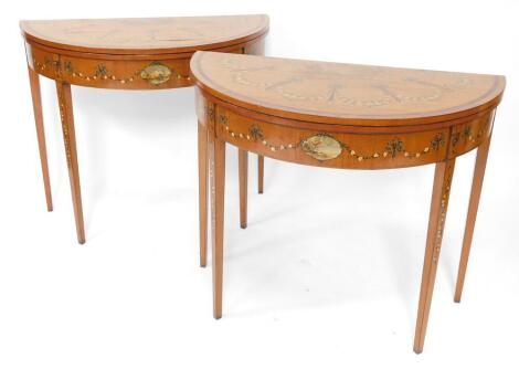 A pair of 19thC Sheraton revival hand painted satinwood demi lune card tables, with baize lined folding tops, oval painted vignettes within painted swags with urns, raised on square taper legs, 77cm high, 46cm deep.
