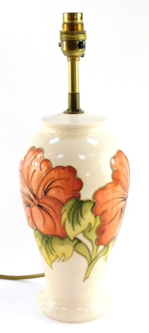 In Display cabinet A Moorcroft pottery table lamp decorated in the Hibiscus pattern, of baluster form, decorated against a cream ground, impressed marks, 38cm high.