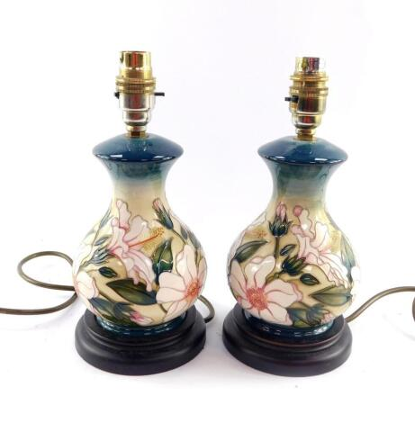 A pair of Moorcroft pottery table lamps decorated with flowers, of baluster form, against a cream to blue ground, 26cm high.