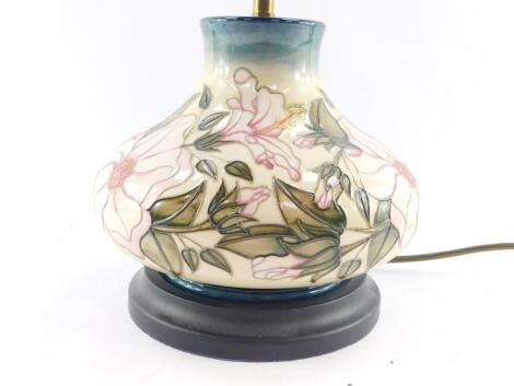 A Moorcroft pottery table lamp decorated in a floral pattern, of baluster form against a cream to blue ground, 27cm high.