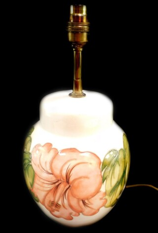 A Moorcroft pottery table lamp decorated in the Hibiscus pattern, of baluster form, against a cream ground, 28.5cm high.