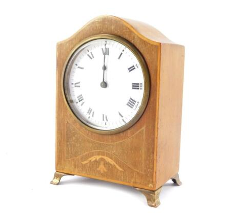 An Edwardian mahogany and inlaid mantel clock, enamel dial bearing Roman numerals, clock work movement, the case of domed form, raised on brass bracket feet, 18cm high, 12cm wide.