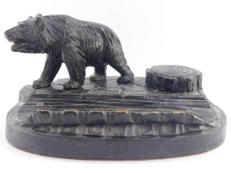 A Black Forest late 19thC desk stand, carved with a bear and a tree stump hinge lidded inkwell, on a naturalistic oval base, 24cm wide.