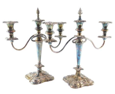 A pair of silver plated three branch candelabra, with drip pans and extinguishers, 37cm high.