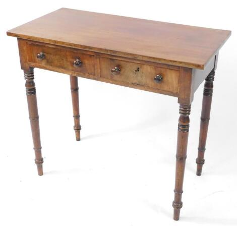 A late Georgian mahogany side table, with two frieze drawers, one lockable, raised on ring turned legs, 74.5cm high, 84.5cm wide, 42.5cm deep.
